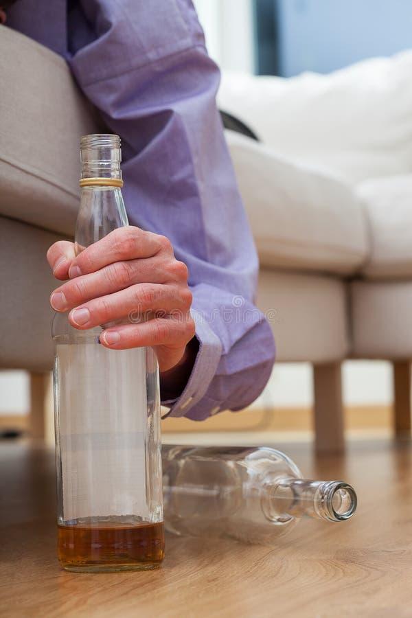 Alcohólico con la botella de vodka imagenes de archivo