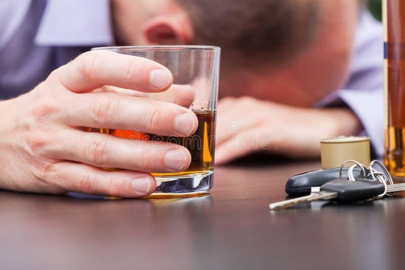 Alcohólico que duerme en la tabla foto de archivo