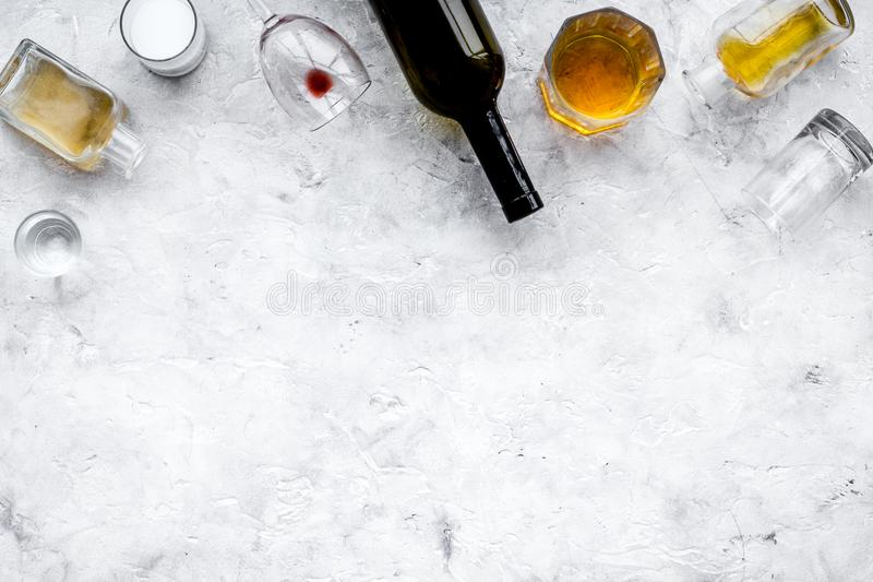 Alcohol abuse. Drunkennes. Glasses and bottles on grey background top view copy space royalty free stock photography