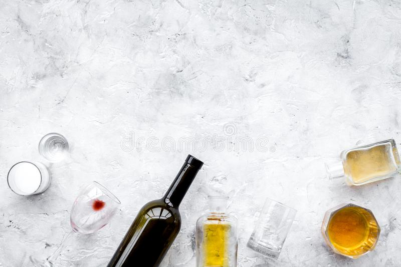 Alcohol abuse. Drunkennes. Glasses and bottles on grey background top view copy space stock photography