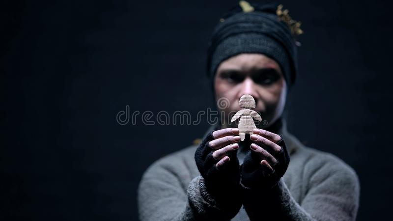 Alcohol addicted homeless showing paper child figure, missing family, loneliness. Stock photo royalty free stock photo