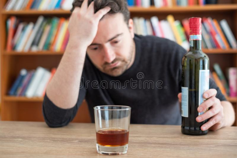 Alcohol addicted man portrait alone with spirit bottle. Depressed man drinking hard liquor at home royalty free stock images