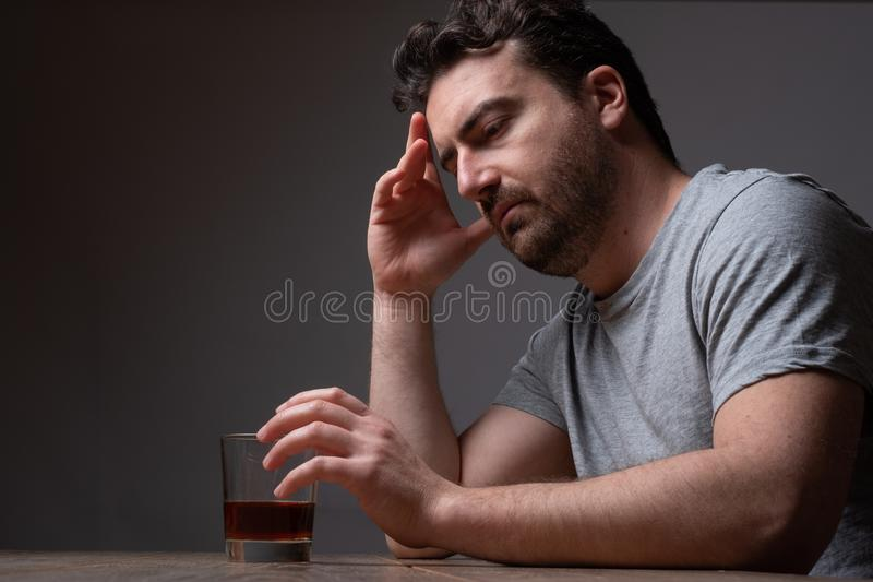 Alcohol addicted man portrait alone with spirit bottle. Depressed man drinking hard liquor at home stock photography