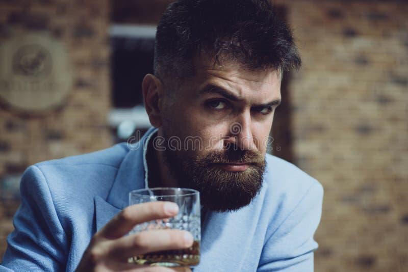 Alcohol addiction. Bearded man drinking alcohol. Whisky, brandy or cognac concept. Serious sad man having alcohol royalty free stock photos