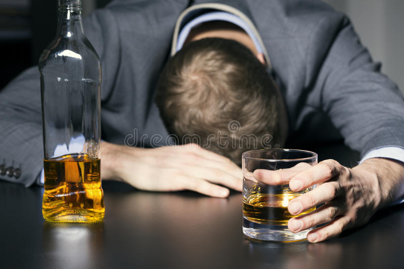 Alcohol addiction - drunk businessman holding a glass of whiskey. On the table stock photo