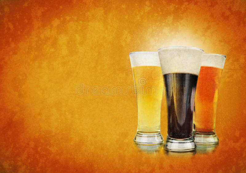Alcohol Beer Glasses on Texture Background. Three beer glasses have foam and are on a golden background with a rough texture. Use it for a Bar or celebration