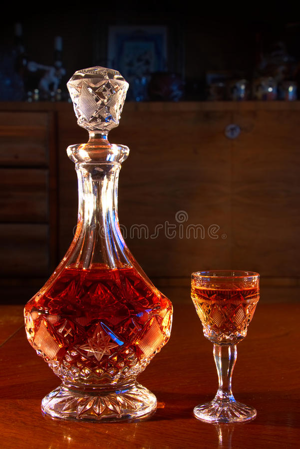 Alcohol in carafe. Crystal decanter and glass full of strong alcoholic drink, carafe and a dram of alcohol on a wooden table, dark living room with antique stock image