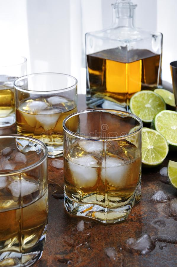 Alcohol cocktail. With brandy, whiskey or rum, lime and ice in glasses royalty free stock image