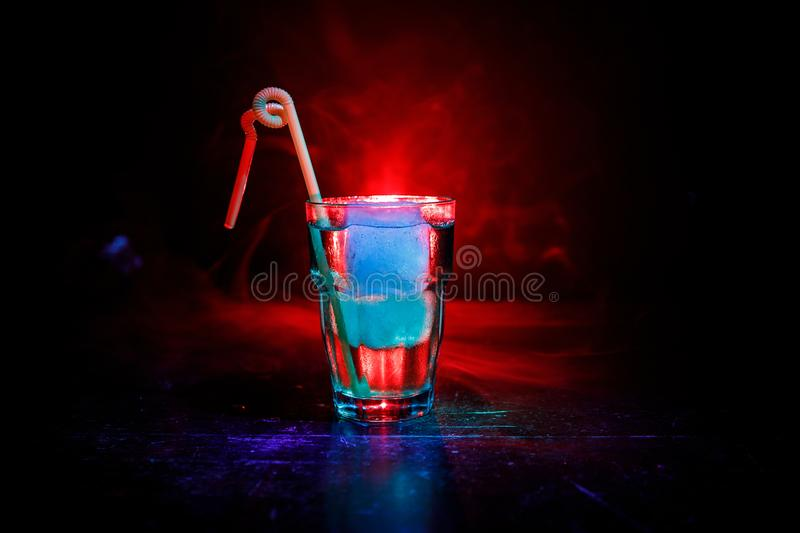 Alcohol cocktail in glass with ice in smoke on dark background. Club drinks concept. One glass of cocktail. Selective focus royalty free stock photography
