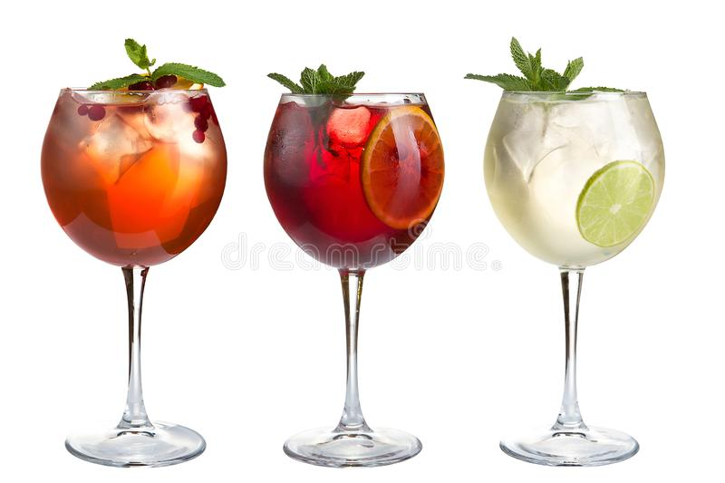 Alcohol cocktail with mint, fruits and berries on a white background. A set of three cocktails in glass goblets on a long stem stock photo