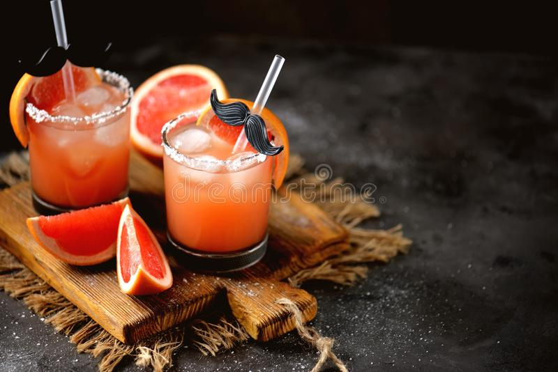 Alcohol cocktail `Salty dog` with vodka, grapefruit fresh, sea salt and ice. stock images