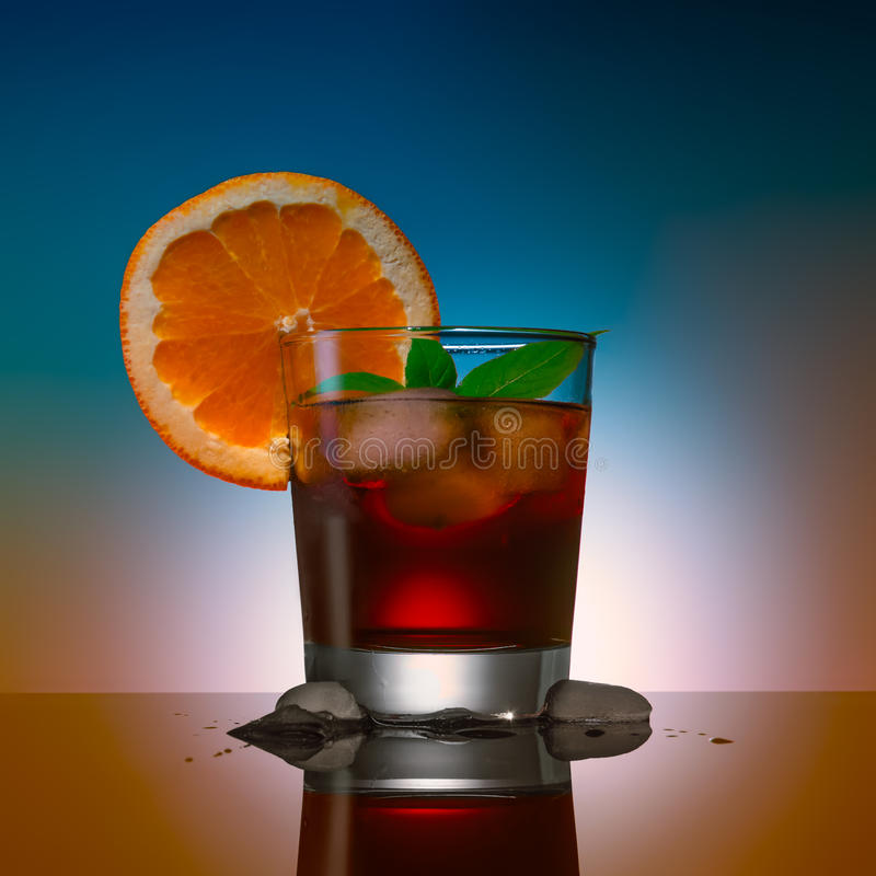 Alcohol coctail drink with ice cubs and orange on a color background royalty free stock image