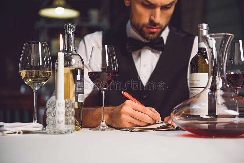Alcohol critic writing his recommendation royalty free stock photo