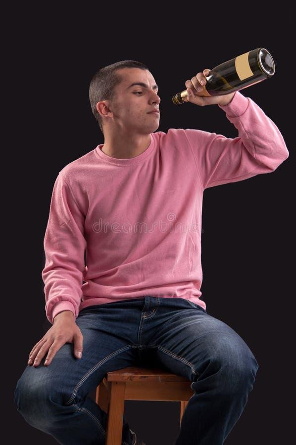 Alcohol de consumición del hombre joven en negro fotografía de archivo libre de regalías