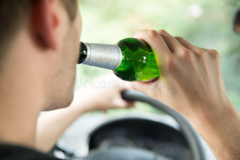 Alcohol de consumición del hombre mientras que conduce el coche fotos de archivo libres de regalías