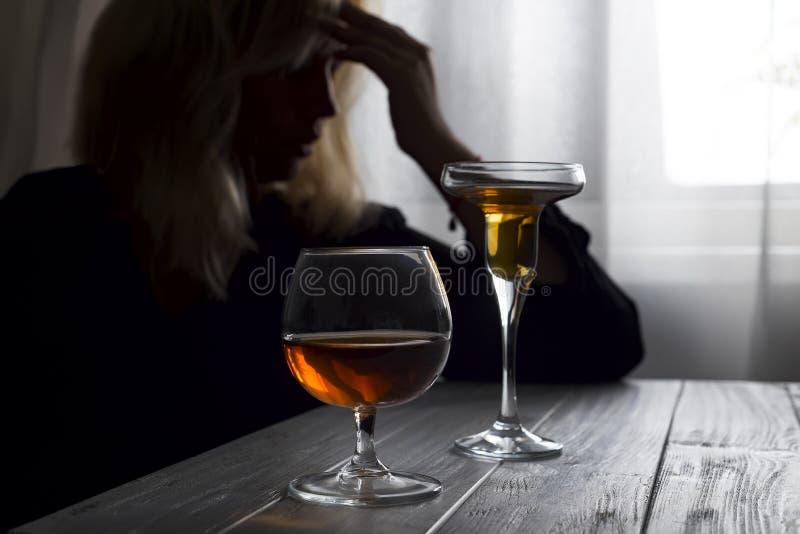 Alcohol de consumición de la mujer solo mirando hacia fuera su ventana Depresión, alcoholismo, concepto solo de la persona Ciento fotos de archivo