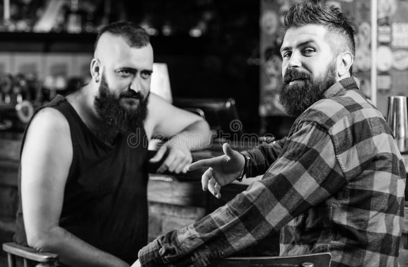 Alcohol de consumici?n del hombre barbudo brutal del inconformista con el amigo en el contador de la barra Hombres que se relajan imagen de archivo