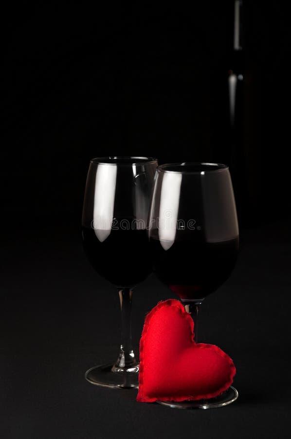 Alcohol de la bebida del vino rojo Dos vidrios del vino rojo y de Toy Heart suave en fondo negro Cena romántica del concepto foto de archivo