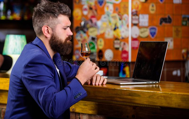 Alcohol de la bebida de la navegación por Internet del hombre de negocios Coñac de consumición en línea del trabajo del freelance fotos de archivo libres de regalías