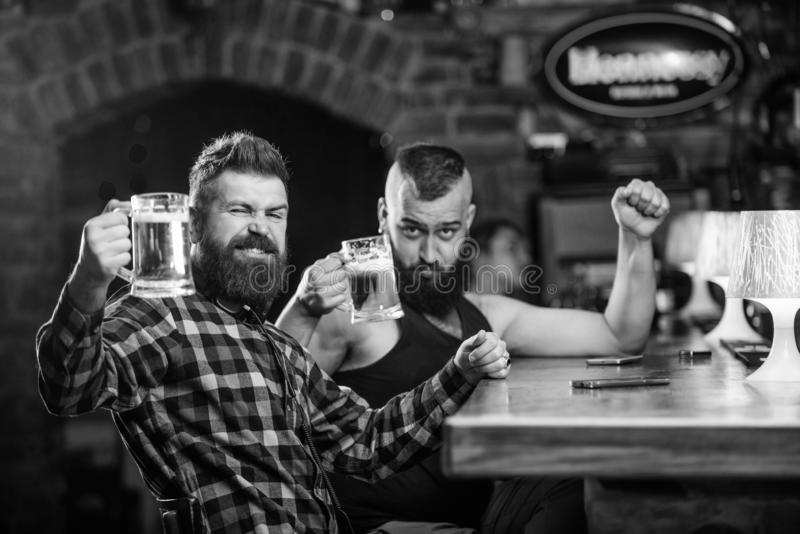 Alcohol drinks. Friends relaxing in pub with beer. Refreshing beer concept. Men drinking beer together. Hipster brutal royalty free stock photo