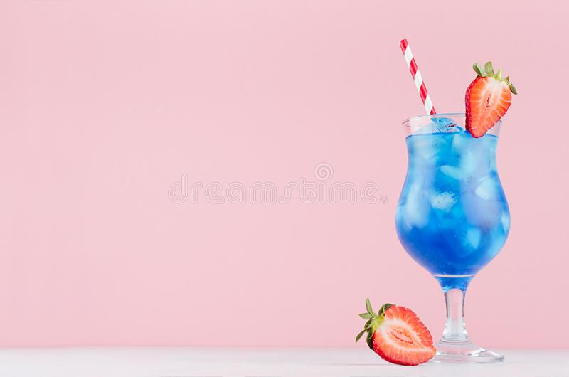 Alcohol juicy fruit blue cocktail with curacao liquor, strawberry slice, ice cubes, straw in frozen wineglass in modern pink. Alcohol juicy fruit blue cocktail royalty free stock photography