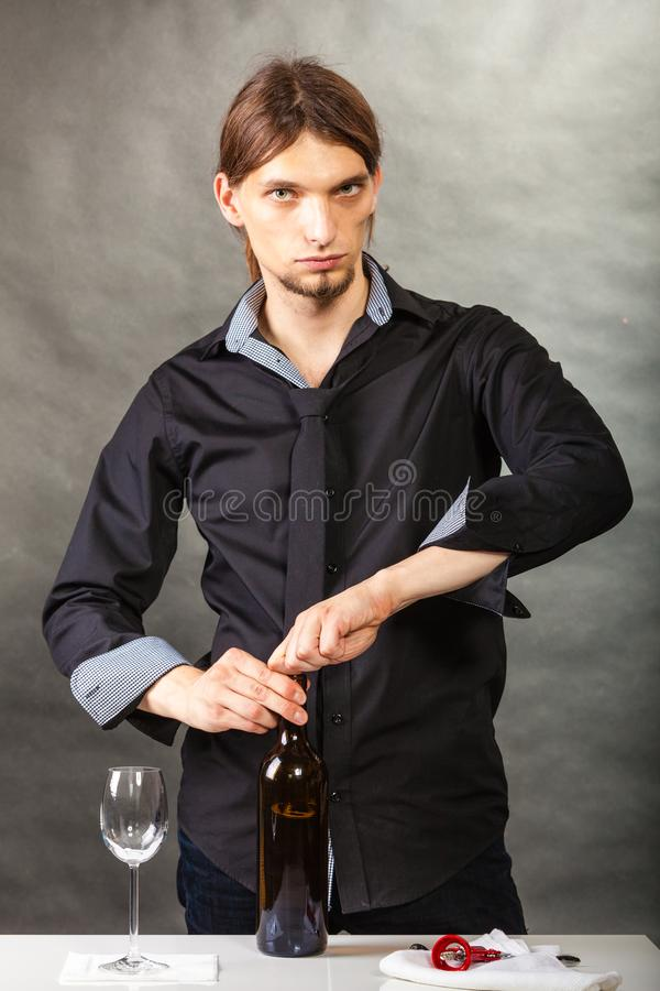 Somellier opening bottle with corkscrew. Alcohol liquor degustation winery relax concept. Somellier opening bottle with corkscrew. Male waiter opens wine royalty free stock images