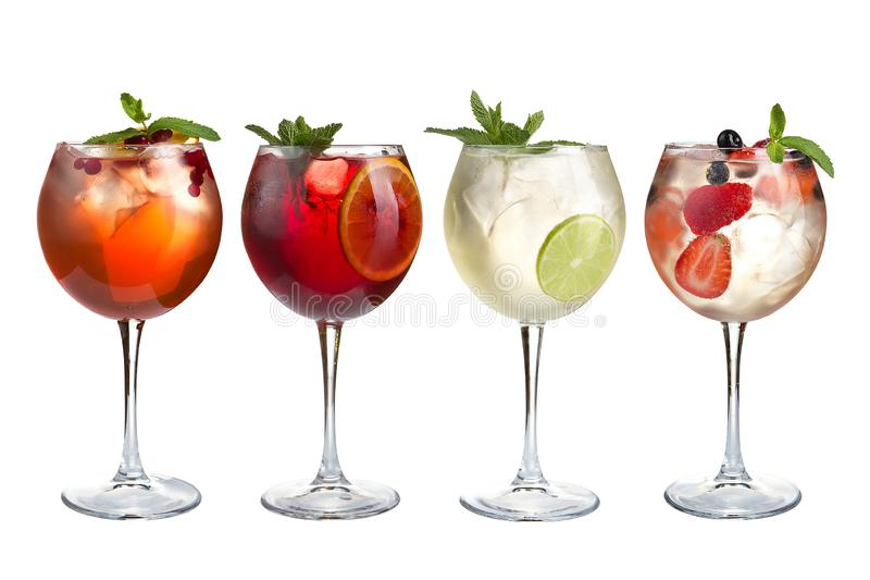 Alcohol refreshing cocktails with mint, fruits and berries on a white background. A set of four cocktails in glass glasses on a royalty free stock photography