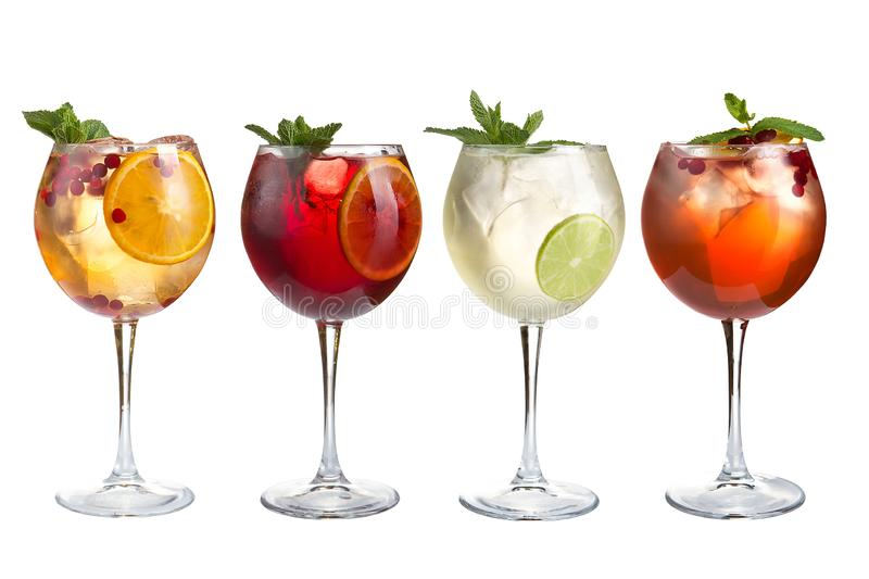Alcohol refreshing cocktails with mint, fruits and berries on a white background. A set of four cocktails in glass goblets royalty free stock photos