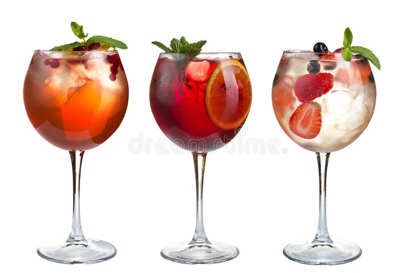 Alcohol refreshing cocktails with mint, fruits and berries on a white background. A set of three cocktails in glass goblets on a stock photography