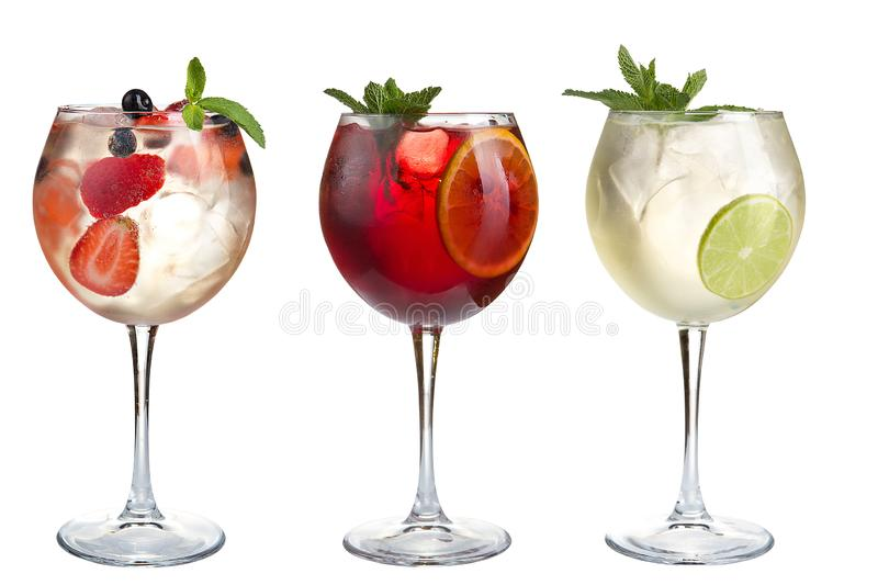 Alcohol refreshing cocktails with mint, fruits and berries on a white background. Set of three cocktails in glass goblets royalty free stock photo