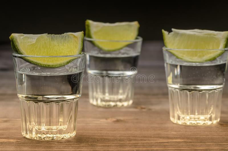 Alcohol shots with a lime on wooden background/Alcohol shots with a lime on wooden background. selective focus stock images