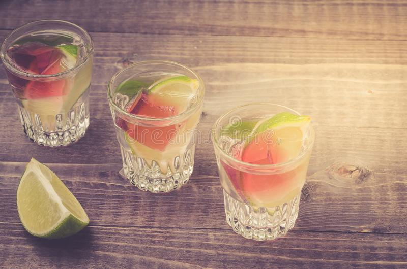 Alcohol shots with a lime/Alcohol shots with a lime on wooden bar counter. Top view royalty free stock photography