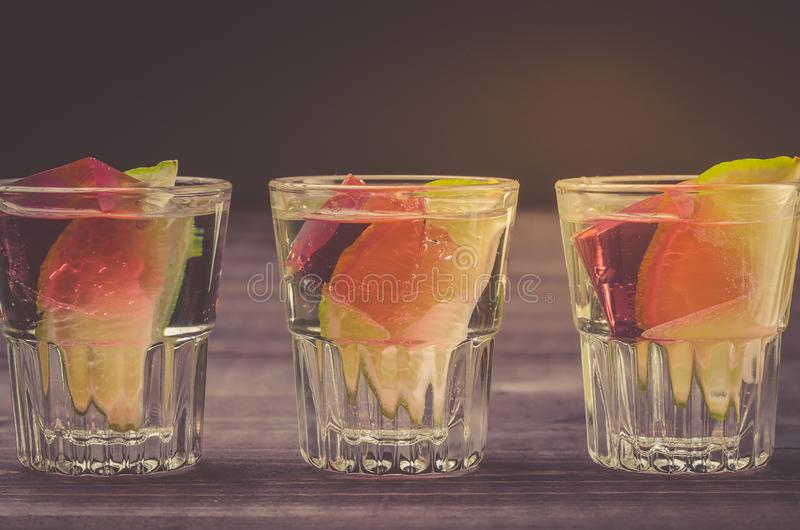 Alcohol shots with a lime on a wooden table/Alcohol shots with a lime on a wooden table. Close up royalty free stock photography