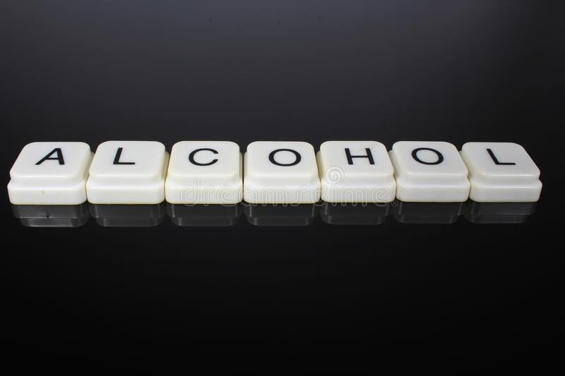 Alcohol text word title caption label cover backdrop background. Alphabet letter toy blocks on black reflective background. White. Alphabetical letters stock images