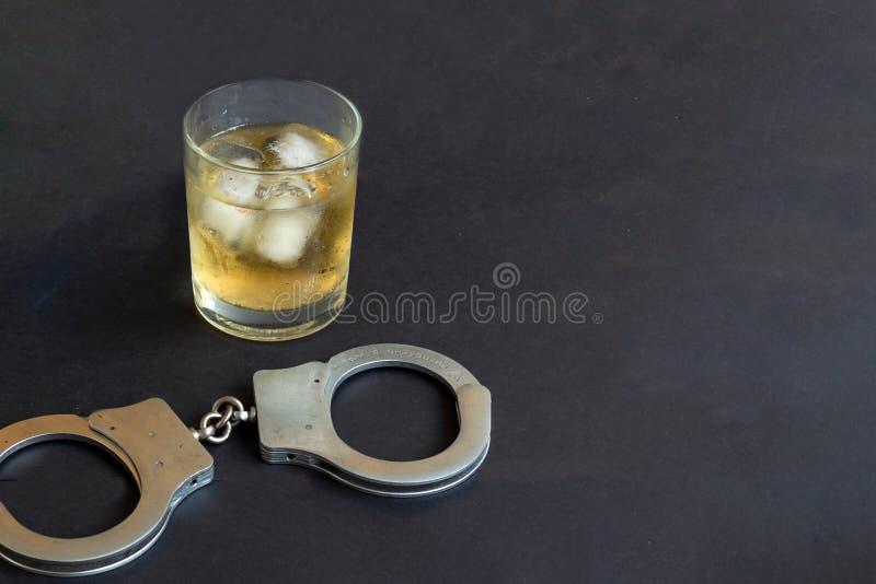 Alcohol y esposas en fondo negro del color fotografía de archivo libre de regalías