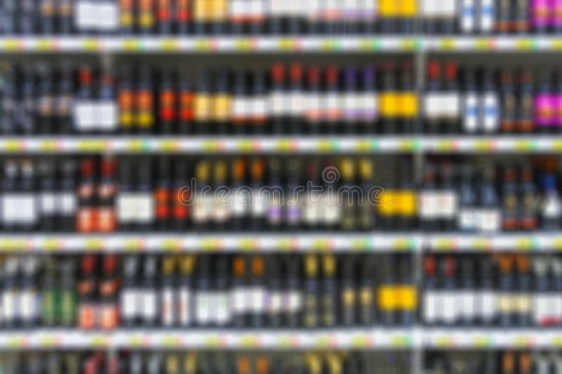 Alcoholic beverages on the shelves in supermarket. As background in blur royalty free stock photography