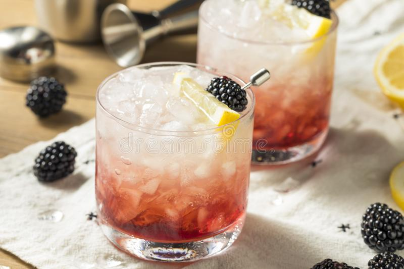 Alcoholic Blackberry Gin Bramble Cocktail. With Lemon royalty free stock photography