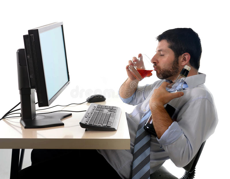 Alcoholic business man drinking whiskey sitting drunk at office with computer. Young alcoholic business man drinking whiskey sitting drunk at office with stock photo