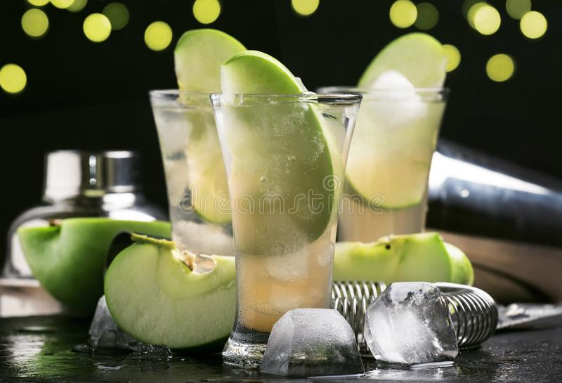 Alcoholic cocktail with dry white vermouth, green apple, juice, soda and ice, black bar counter background, selective focus. Alcoholic cocktail with dry white stock images