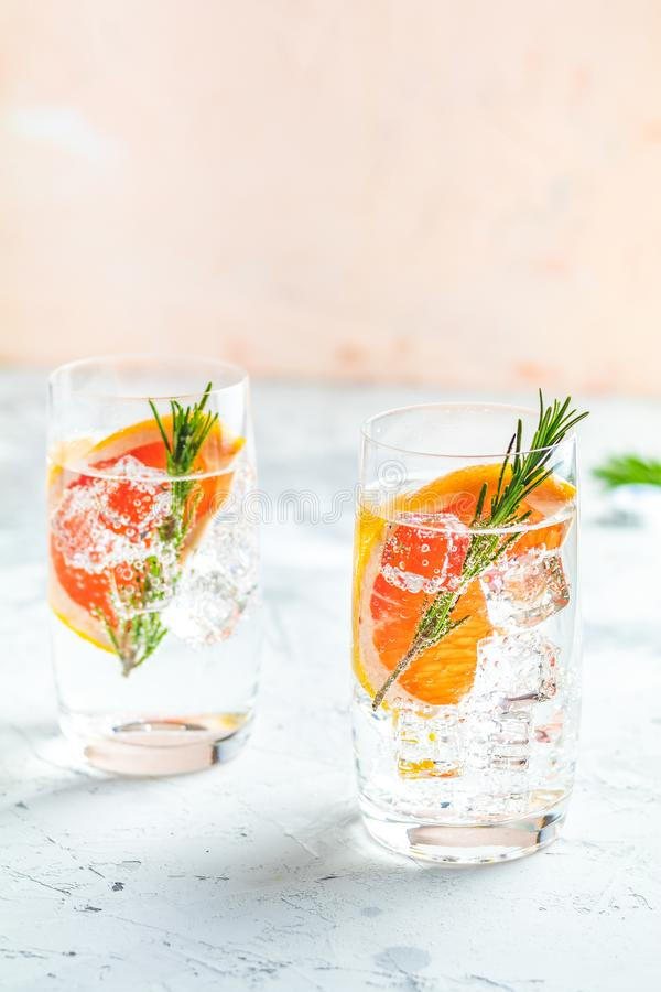 Alcoholic cocktail with grapefruit, soda, ice, gin and rosemary. Light gray concrete table background, selective focus, shallow depth of the field royalty free stock images