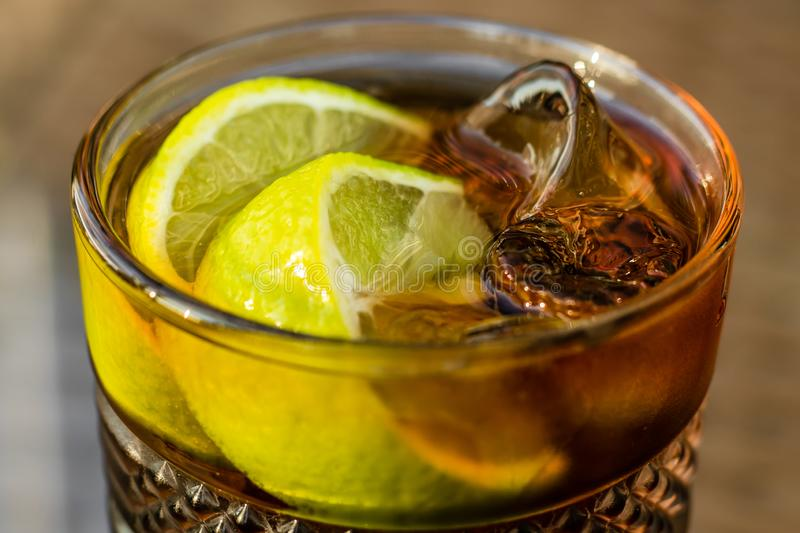 Alcoholic cocktail - Long Island Iced Tea. Iced tea with lemon in glass, close-up. A brown sweet drink. royalty free stock image
