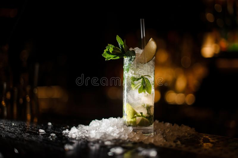 Alcoholic cocktail mojito stands on a bar counter. Alcoholic cocktail mojito, strewn with chipped ice, stands on a bar counter on a dark wooden background royalty free stock images