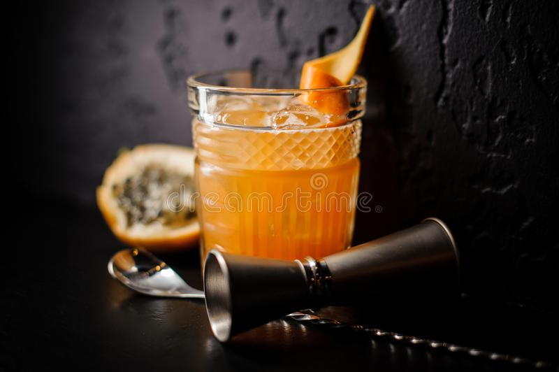 Alcoholic cocktail of orange color with ice and citrus stands on a black background. Alcoholic cocktail of orange color in a stylish glass with ice and citrus royalty free stock images