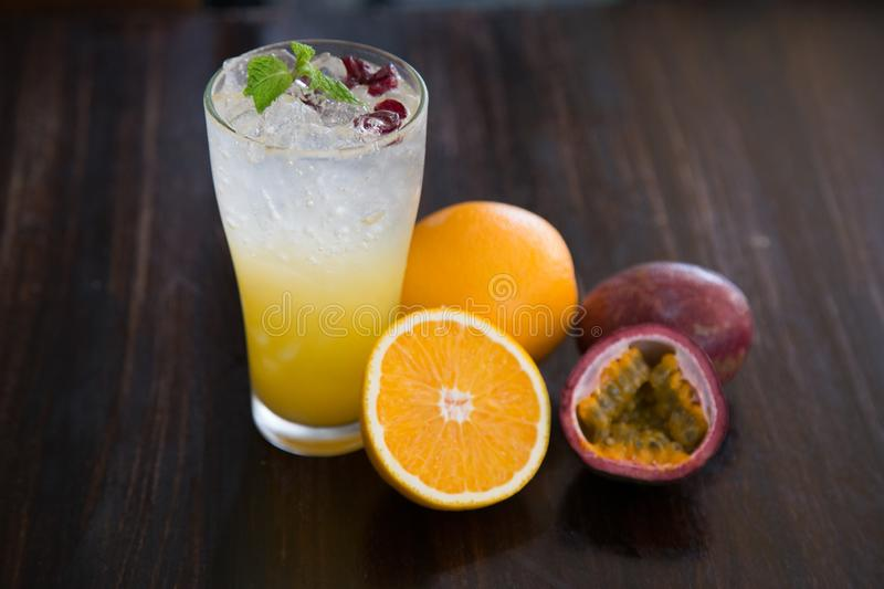 Tropical cocktail with passion fruit, orange and mint on a dark background. Alcoholic cocktail with orange and passion fruit stock photography