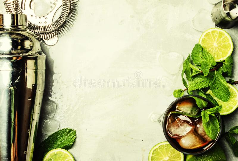 Alcoholic cocktail with rum, cola, ice and mint, bar tools, drink background, top view stock image