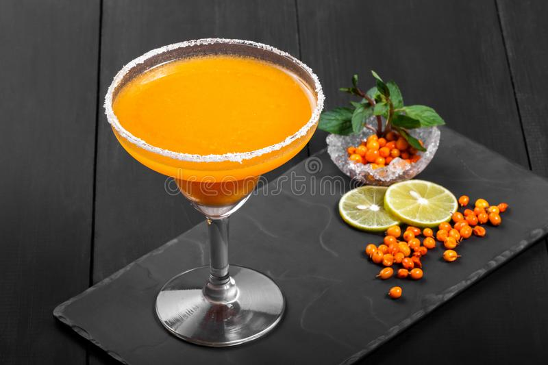 Alcoholic cocktail with sea buckthorn in a glass on dark background. Summer drinks and cocktails stock image