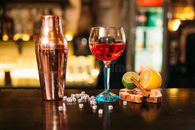 Alcoholic cocktail, shaker and dice on bar counter royalty free stock photography