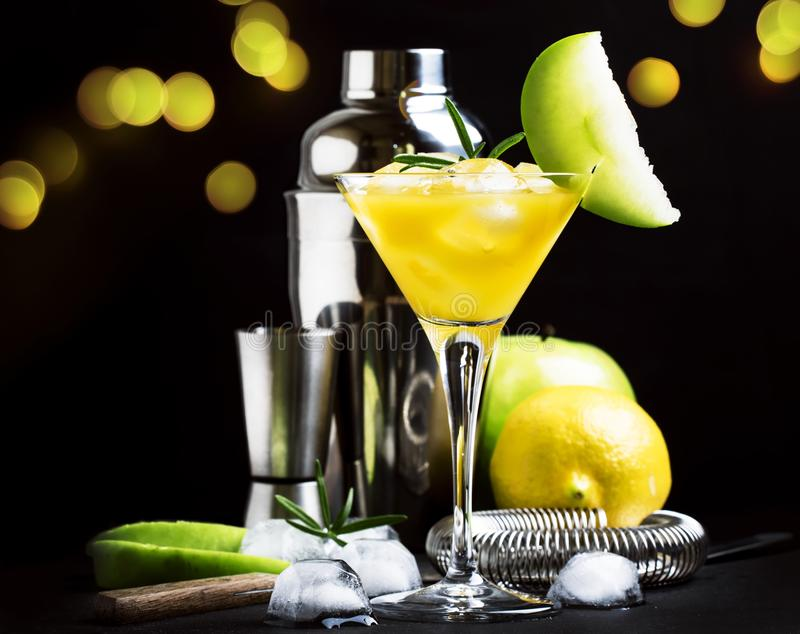 Alcoholic cocktail with vermouth, green apple, juice, soda and ice, black background, selective focus royalty free stock photos
