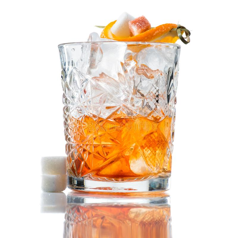 Alcoholic cocktail with whiskey, orange and a slice of sugar. Isolated on white background stock image