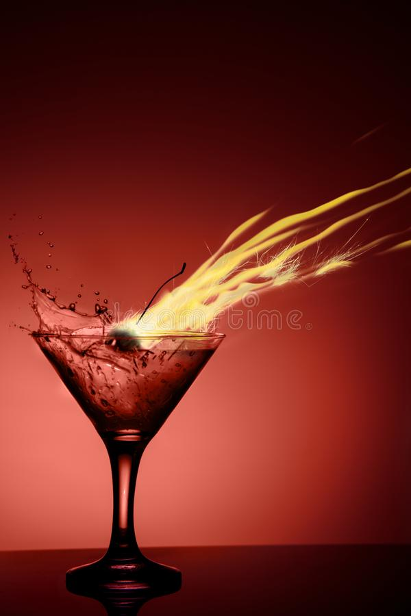Alcoholic coctail with a flame and a splash on red background royalty free stock photography